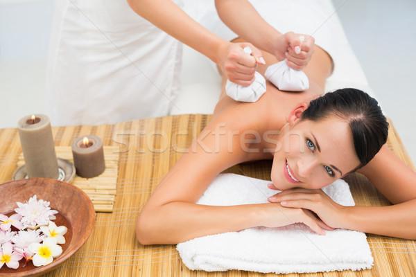 Peaceful brunette enjoying a herbal compress massage smiling at  Stock photo © wavebreak_media