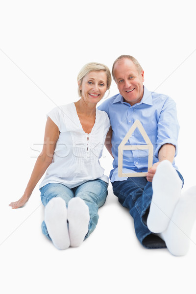 Happy mature couple holding a house shape Stock photo © wavebreak_media