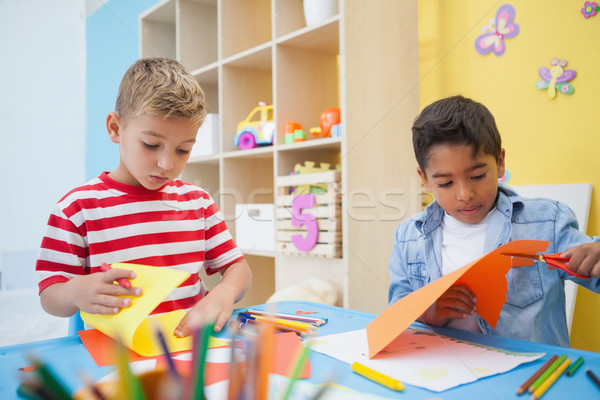 Cute little boys cutting paper shapes in classroom Stock photo © wavebreak_media