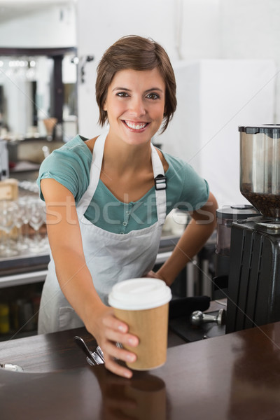Pretty barista smiling at camera holding disposable cup Stock photo © wavebreak_media