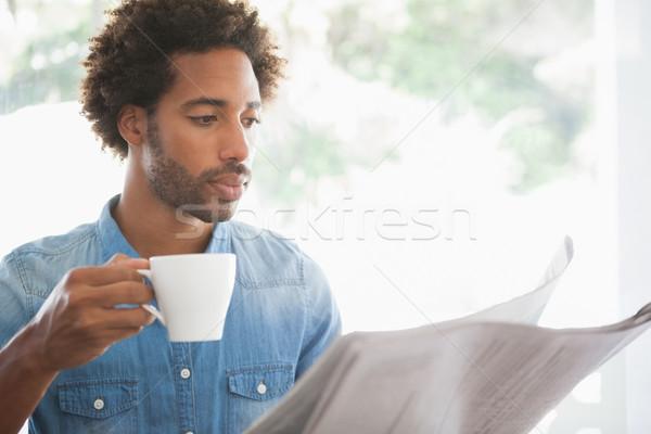 Casual man having coffee while reading newspaper Stock photo © wavebreak_media