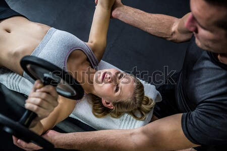 Stock photo: Personal trainer helping client lift dumbbells