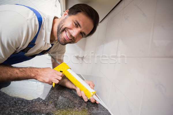 Plumber putting filling in between tiles Stock photo © wavebreak_media
