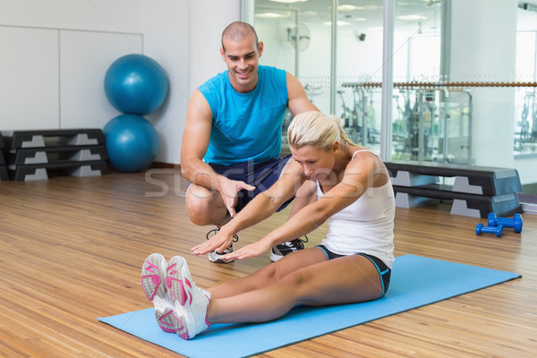 Trainer assisting woman with exercises at fitness studio Stock photo © wavebreak_media