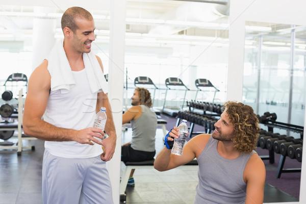 Uśmiechnięty trener mówić dopasować człowiek siłowni Zdjęcia stock © wavebreak_media