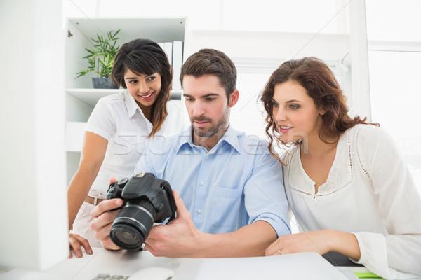 Teamwork holding digital camera and interacting Stock photo © wavebreak_media