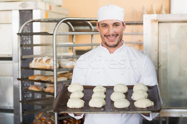 Smiling baker holding tray of raw dough Stock photo © wavebreak_media