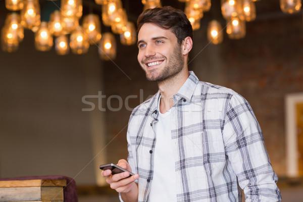 Young man sending a text Stock photo © wavebreak_media