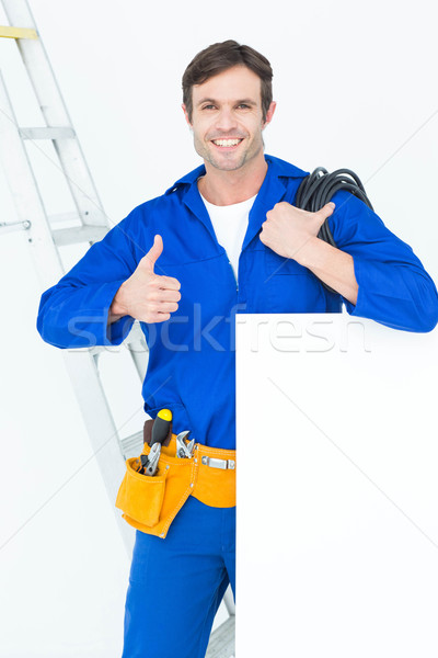 Electrician with wire and bill board gesturing thumbs Stock photo © wavebreak_media