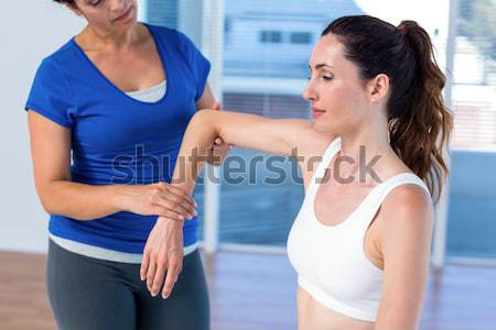Woman working on exercise mat with her trainer  Stock photo © wavebreak_media