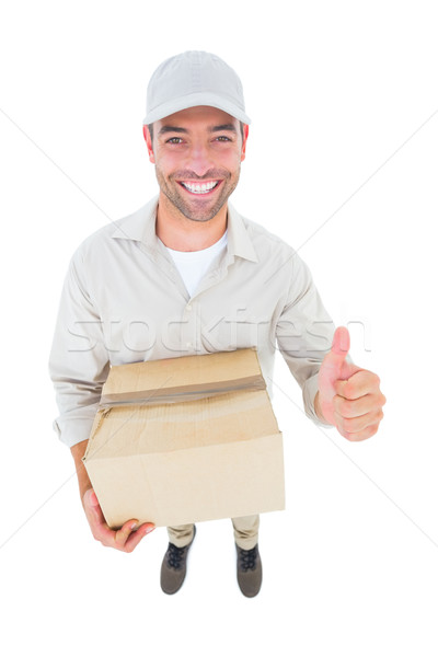 Handsome delivery man with cardboard box gesturing thumbs up Stock photo © wavebreak_media