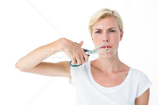 Séduisant femme blonde cigarette ciseaux blanche Photo stock © wavebreak_media