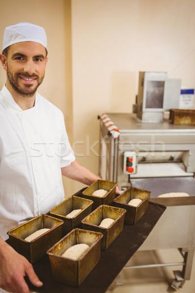 Happy baker holding tray of loaf tins Stock photo © wavebreak_media