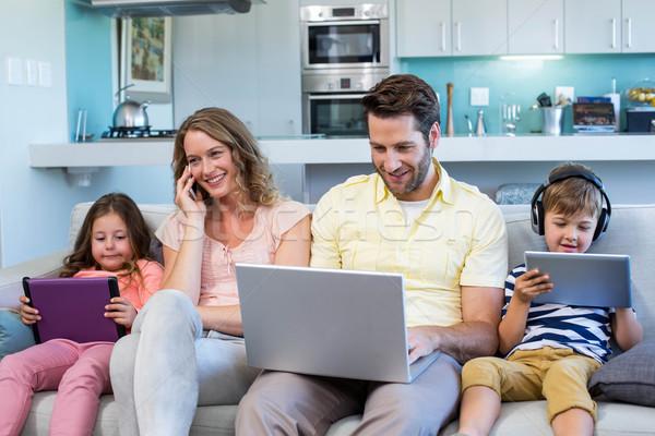 Família feliz sofá juntos dispositivos casa sala de estar Foto stock © wavebreak_media