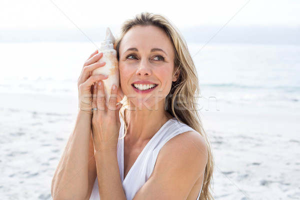 Smiling blonde in white dress listening the seashell Stock photo © wavebreak_media