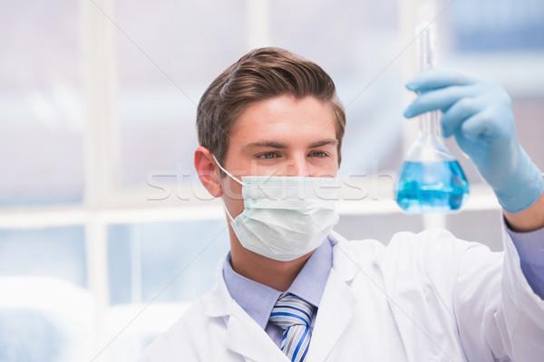 Wetenschapper onderzoeken beker Blauw vloeistof laboratorium Stockfoto © wavebreak_media