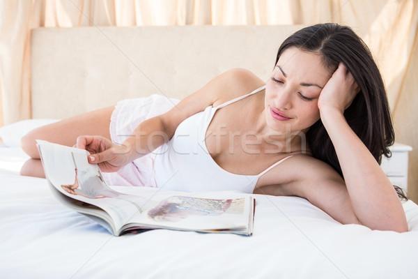 Pretty brunette reading a magazine on bed Stock photo © wavebreak_media