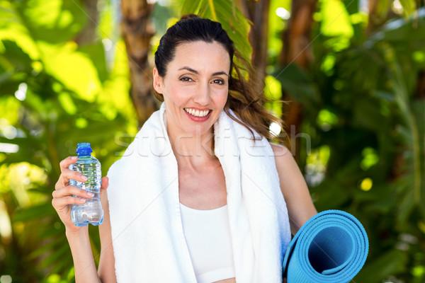 Smiling brunette holding bottle of water and exercise mat Stock photo © wavebreak_media