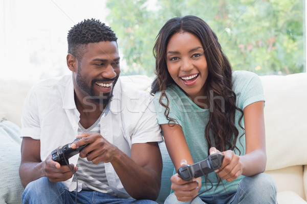 Stock photo: Happy couple on the couch playing video games