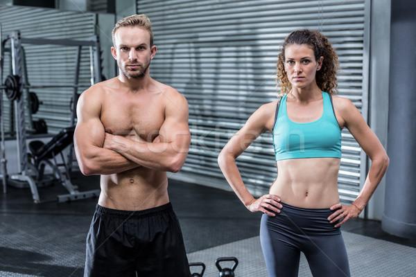 Muskularny para patrząc kamery crossfit siłowni Zdjęcia stock © wavebreak_media