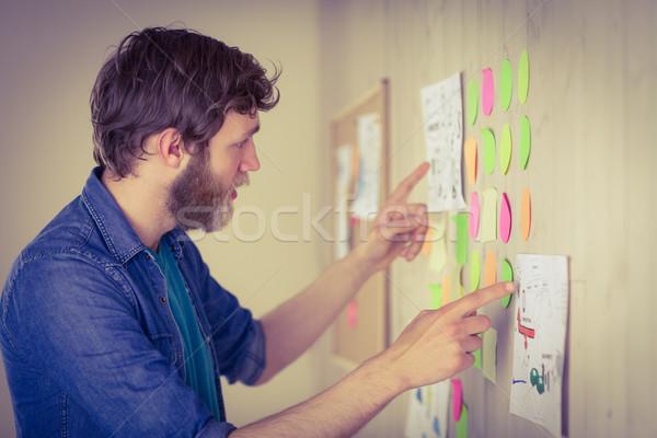 Bearded hipster looking at brainstorm wall Stock photo © wavebreak_media