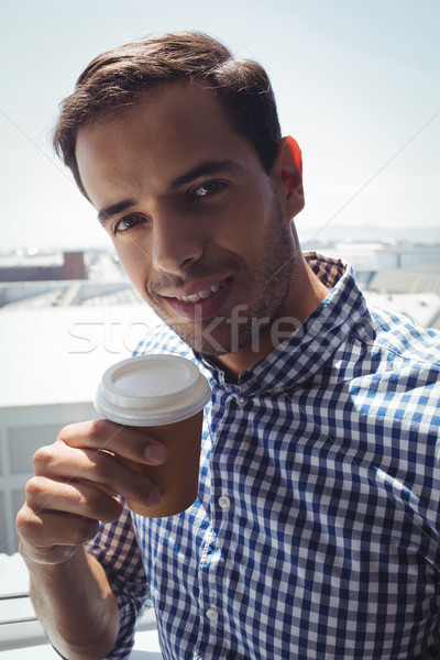 Thoughtful young businessman holding coffee cup by window in office Stock photo © wavebreak_media