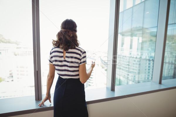 Nadenkend uitvoerende permanente venster kantoor vrouw Stockfoto © wavebreak_media