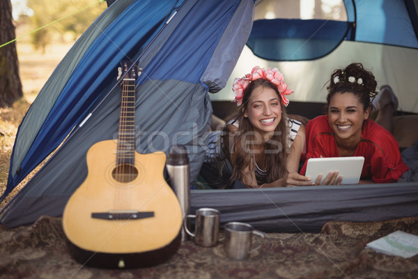 Stock photo: Smiling female friends relaxing in tent