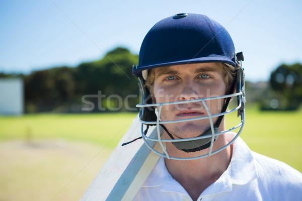 Portrait of cricket player holding bat while wearing helmet at field Stock photo © wavebreak_media