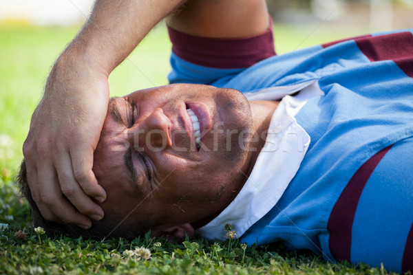 Injured rugby player with eyes closed lying on field Stock photo © wavebreak_media