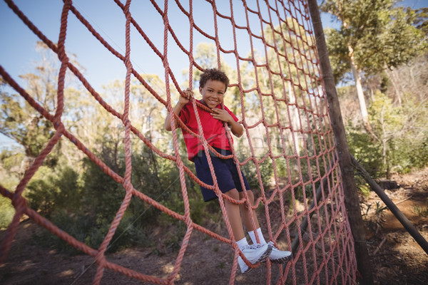 Portrait of happy boy climbing a net during obstacle course Stock photo © wavebreak_media