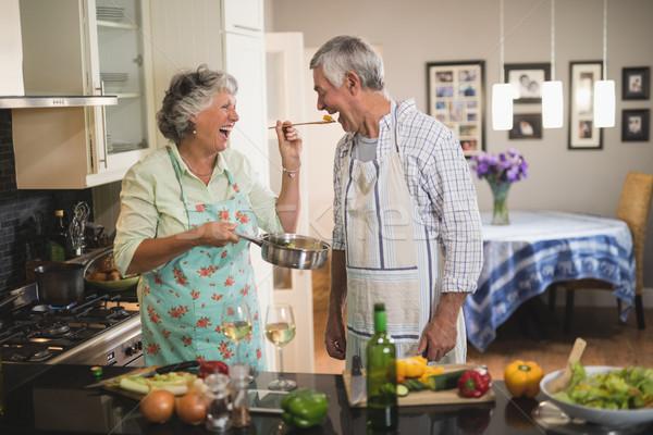 Cheerful senior woman feeding man in kitchen Stock photo © wavebreak_media