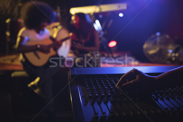 Hand operating sound mixer while musicians practicing in nightclub Stock photo © wavebreak_media