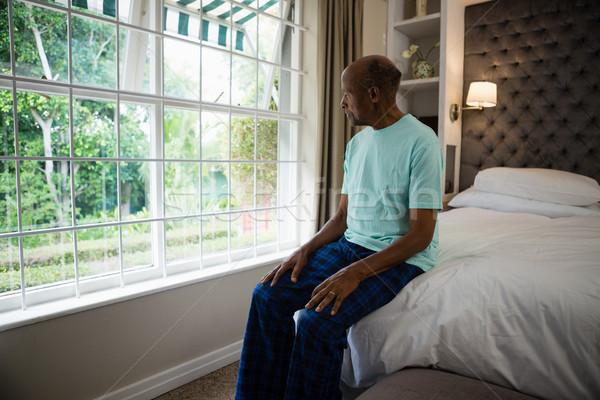 Thoughtful senior man sitting by window in bedroom Stock photo © wavebreak_media