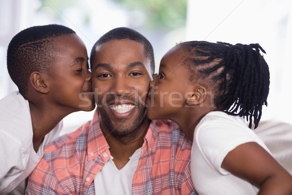 Children kissing smiling father at home Stock photo © wavebreak_media