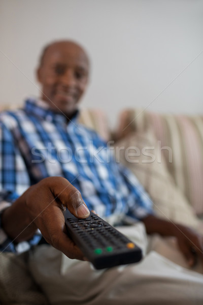 Smiling senior man holding remote control Stock photo © wavebreak_media