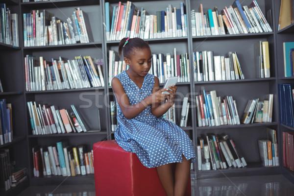 девушки мобильного телефона сидят книжная полка библиотека телефон Сток-фото © wavebreak_media