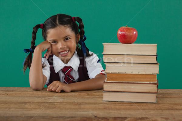 Schoolgirl sitting beside books stack with apple on top against chalkboard Stock photo © wavebreak_media
