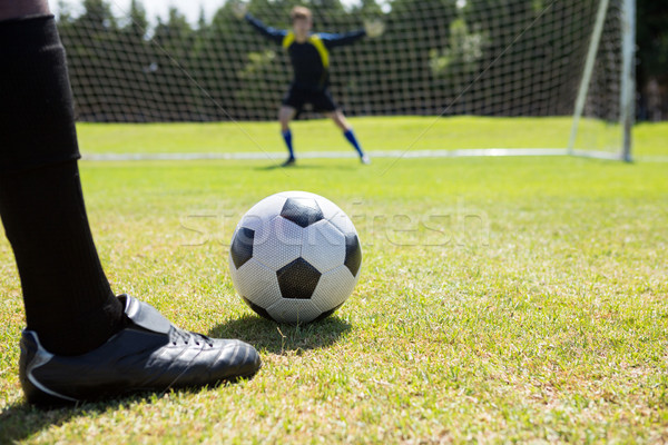 Low section of soccer player with ball against goalkeeper Stock photo © wavebreak_media