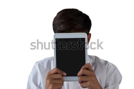 Teenage boy hiding his face behind digital tablet Stock photo © wavebreak_media