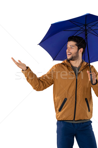 Smiling man standing under umbrella Stock photo © wavebreak_media