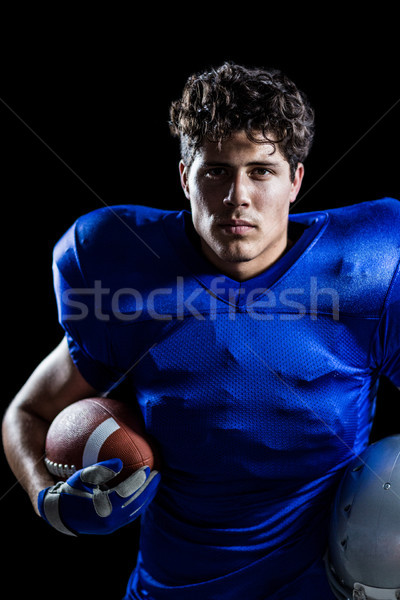 Portrait of serious American football player holding ball and he Stock photo © wavebreak_media