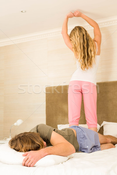 Pretty woman outstretching her arms while boyfriend sleeping Stock photo © wavebreak_media