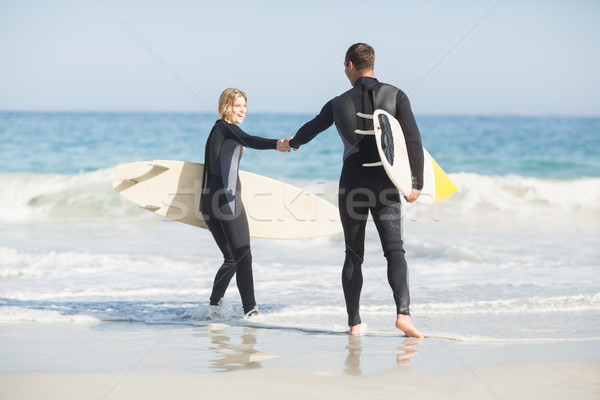 Couple with surfboard holding hand on the beach Stock photo © wavebreak_media