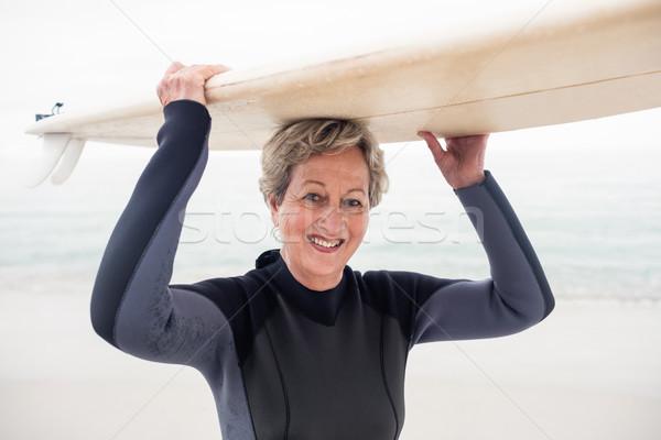 Portrait of senior woman in wetsuit carrying surfboard over head Stock photo © wavebreak_media