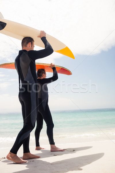 Father and son carrying a surfboard over their head Stock photo © wavebreak_media