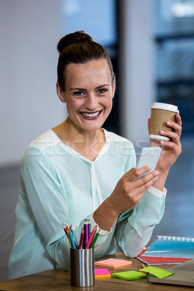 Nő tart kávéscsésze sms üzenetküldés mobiltelefon iroda Stock fotó © wavebreak_media