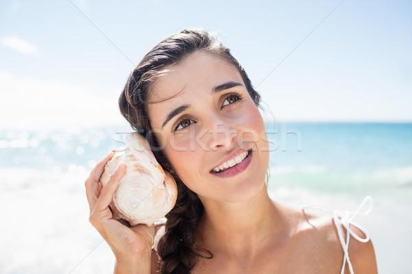 Portret uśmiechnięta kobieta słuchania skorupiak plaży kobieta Zdjęcia stock © wavebreak_media