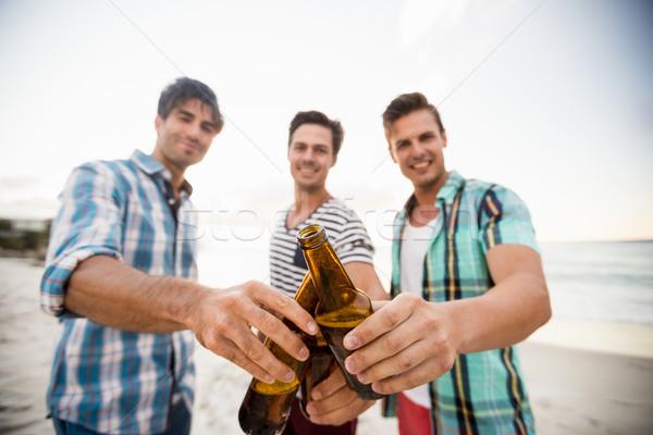 Barátok éljenez sör tengerpart víz férfi Stock fotó © wavebreak_media