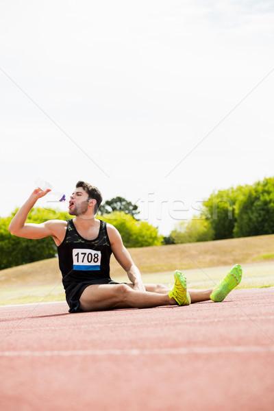 Zmęczony sportowiec posiedzenia uruchomiony utwór woda pitna Zdjęcia stock © wavebreak_media
